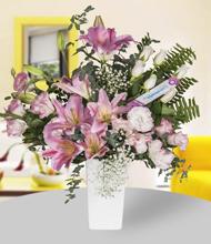 Seramik vazoda pembe lilyum, beyaz güller ve lisyantus