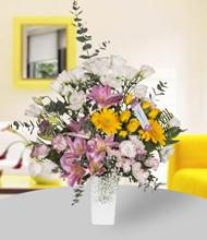 Seramik vazoda pembe lilyum, sarı güller ve lisyantus